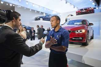 U.S. Olympian and gold medal winning decathlete Bryan Clay is interviewed by local Detroit ABC affiliate WXYZ-TV following the BMW press conference at the North American International Auto Show in Detroit on January 9, 2012.  Clay, along with fellow Olympians Apolo Anton Ohno and Janet Evans joined BMW executives to help unveil the all-new 2012 BMW 3 Series Sedan which made its world debut at the show.