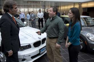 BMW of North America President and CEO Ludwig Willisch,left, personally delivers the first BMW ActiveE in the U.S. to Tom and Meredith Moloughney of Chester, NJ at BMW NA's headquarters in Woodcliff Lake, NJ  on Friday, January 13, 2012.  The Moloughneys are the first of what will be 700 households in the U.S. who will lease a BMW ActiveE for a two year period and provide feedback towards the development of the BMW i3 which will come to market in 2013. The couple previously leased a MINI E, pictured in the background, and drive the vehicle over 72,000 miles.