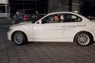 Tom Moloughney of Chester, NJ gives the thumbs up as he and his wife, Meredith, drive away after taking delivery of the first BMW ActiveE in the US at BMW NA's headquarters in Woodcliff Lake, NJ  on Friday, January 13, 2012. He and his wife, Meredith are the first of what will be 700 households in the U.S. who will lease a BMW ActiveE for a two year period and provide feedback towards the development of the BMW i3 which will come to market in 2013. e development of the BMW i3 which will come to market in 2013.