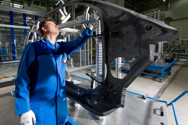 BMW Plant Landshut: new innovation and production centre for CFRP - an employee controls the quality of a CFRP body part (side frame) (03/2012)