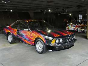 """ART DRIVE! The BMW Art Car Collection 1975-2010"" in London, July 21 - August 4, 2012. From left: Ernst Fuchs, BMW Art Car, 1982 - BMW 635i CSi, Jeff Koons, BMW Art Car, 2010 - BMW M3 GT2."