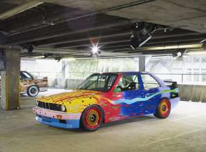 """ART DRIVE! The BMW Art Car Collection 1975-2010"" in London, July 21 - August 4, 2012. From left: Michael Jagamara Nelson, BMW Art Car, 1989 - BMW M3 group A racing version, Ken Done, BMW Art Car, 1989 - BMW M3 group A racing version."