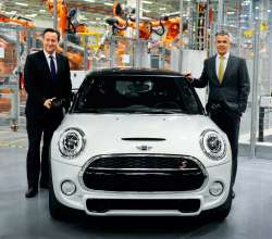 British Prime Minister David Cameron, right, with Peter Schwarzenbauer, BMW Group's board member for MINI, BMW Motorrad, Rolls-Royce, Aftersales BMW Group, with the new MINI.