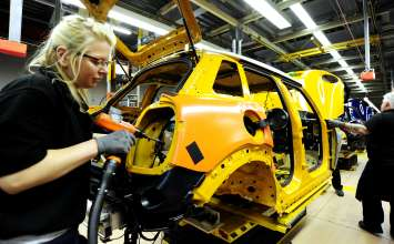 Associates working on the MINI 5-door at the first production line in Plant Oxford's assembly hall.
