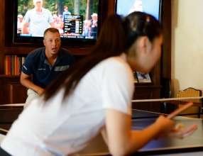PGA TOUR Player Freddie Jacobson challenges Team USA Table Tennis player Lily Zhang in the Cherry Hills Country Club Men's Locker Room during the 2014 BMW Championship in Cherry Hills Village, Colo. Lily Zhang is the 2012 U.S. National Champion in Women's Singles. (09/2014)